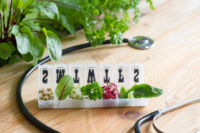 Vegetable sprouts and herbs in the box healthy life style and alternative medicine concept. On wooden background stock photos