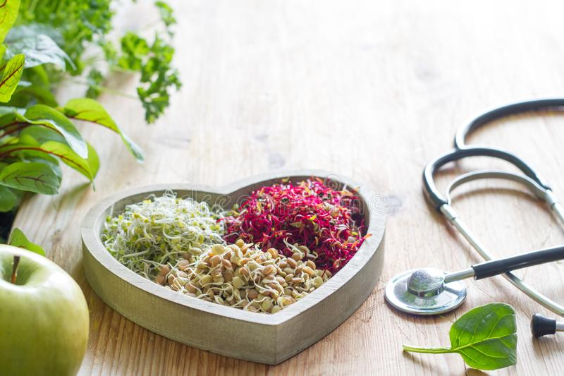 Vegetable sprouts and herbs in the heart healthy life style and alternative medicine concept. On wooden table royalty free stock photo