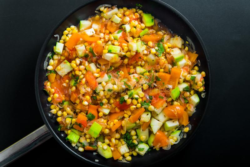 Vegetable stew from dairy corn, young zucchini, orange bell pepper, tomatoes, parsley and onion are cooked in a frying pan. On a black background, closeup, top royalty free stock image