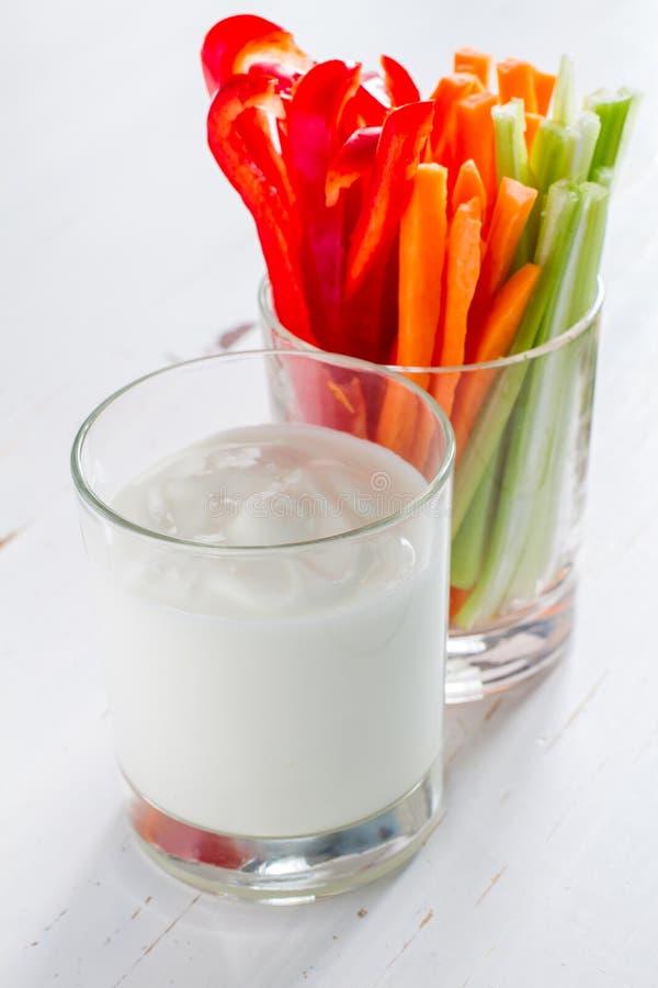 Vegetable sticks and yogurt dip. White wood background stock image