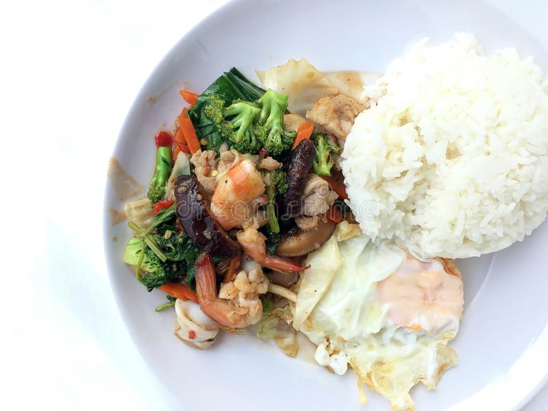 Vegetable stir-fry dish with Thai healthy food stir-fried broccoli, mushroom, carrot, hearb, squid and shrimp with rice and fried stock photography