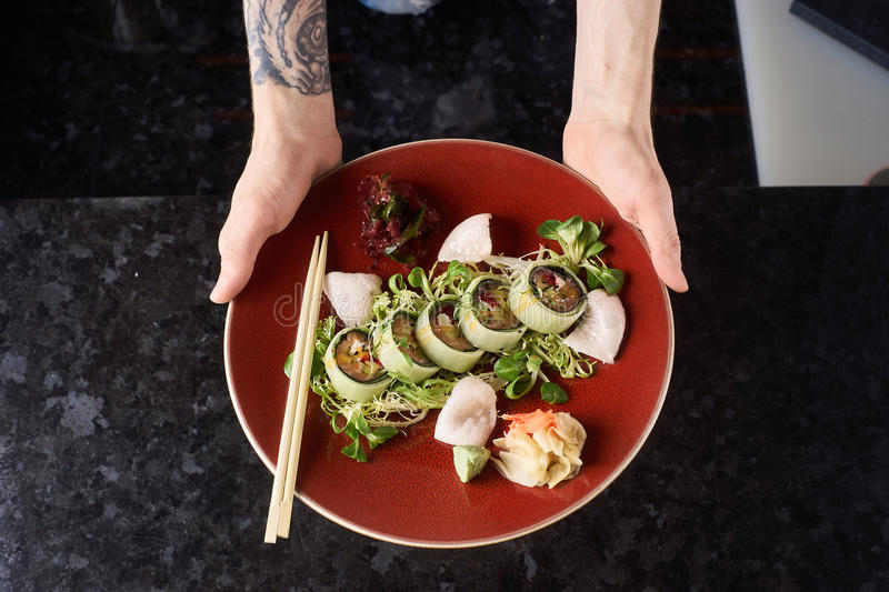 Vegetable sushi rolls with fish. Sushi roll with salmon, avocado, tuna fish, sesame and cream cheese served on red plate with fresh lettuce on black marble royalty free stock photos