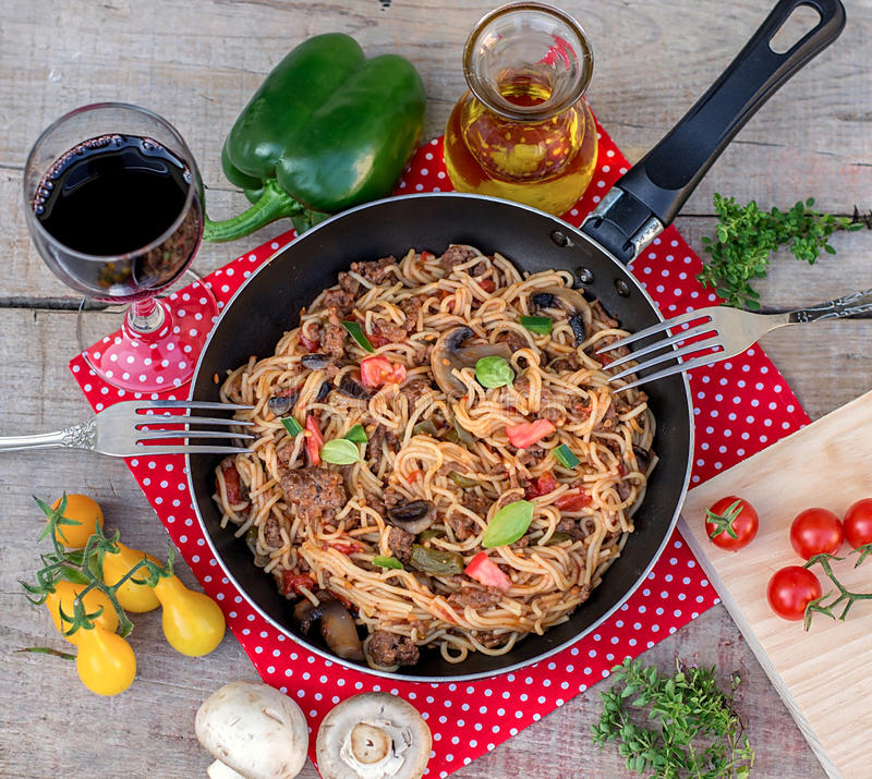 Vegetables, beef and noodles skillet with mushrooms. On wooden background stock images
