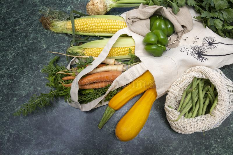 Vegetables with beige eco-friendly bags. Chili pepper, fresh herbs, zucchini, corn, beans, carrots. Zero waste concept royalty free stock photography