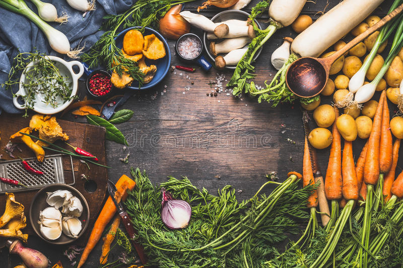Vegetables cooking ingredients for tasty vegetarian dishes. Carrot , potato , onion , mushrooms , garlic , thyme , parsley on dark stock photos