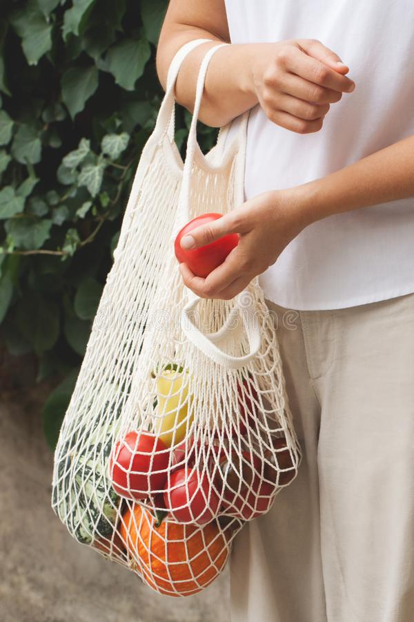 Vegetables in an eco bag and girl`s hands stock photo