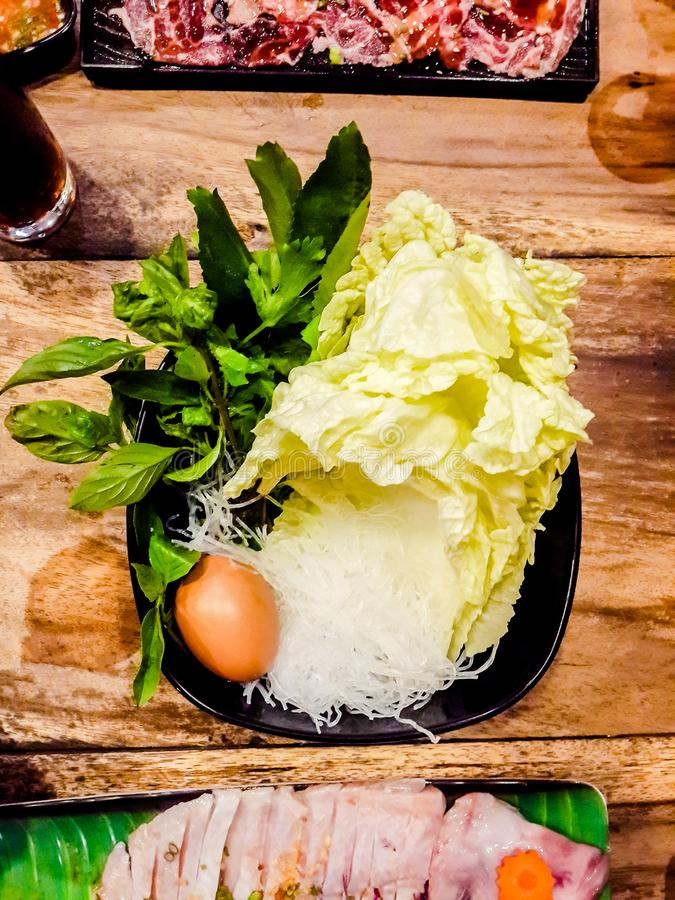 Vegetables and Eggs in a Cup,Sukiyaki and shabu soup with, white cabbage,  vermicelli, fish, and in a white cup on wooden royalty free stock image