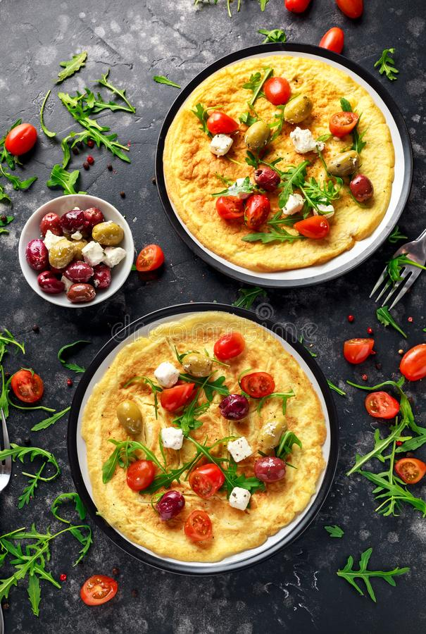 Vegetables Eggs Omelette with tomatoes, wild rocket, greek cheese, olives in a plate. Morning breakfast. healthy food.  stock image