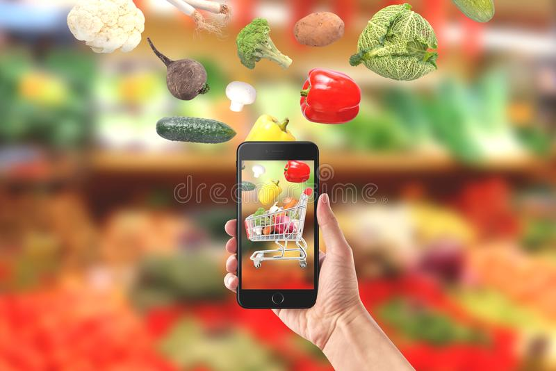 Vegetables fall in mobile phone. Buying fresh organic vegetables concept.  stock image