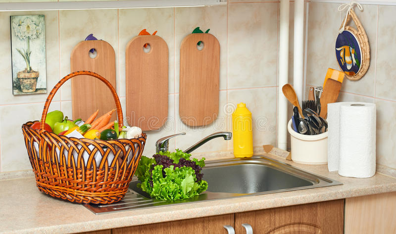 Vegetables and fresh greens in basket in kitchen interior, healthy food concept stock photos