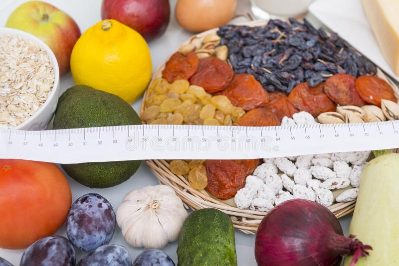 vegetables and fruits with measuring tape, avocado, plums, onion royalty free stock photography