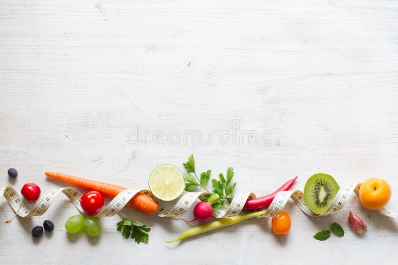 Vegetables and fruits between measuring tape on white background. Healthy diet concept royalty free stock photography