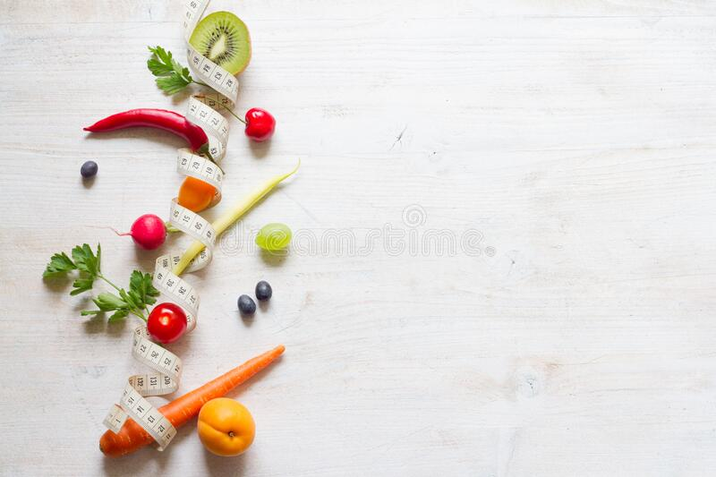 Vegetables and fruits between measuring tape on white background. Healthy diet concept stock photo