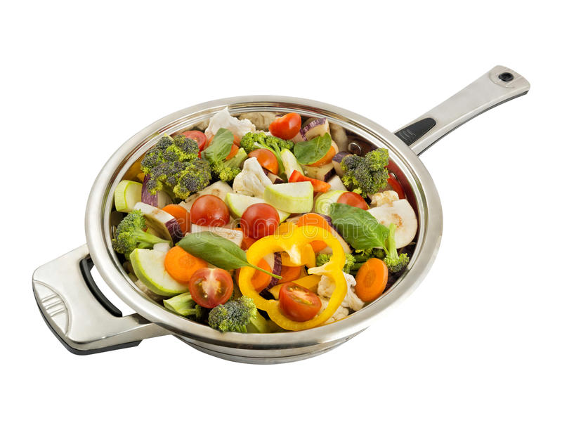 Vegetables in the frying pan. Vegetables in the steel frying pan isolated on white background stock photo