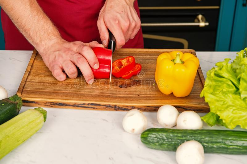 Vegetables getting cut on wooden cutting board. Hand slice pepper with ceramic knife. Food preparation and cooking. Recipes. Vegetarian menu and healthy diet royalty free stock photos