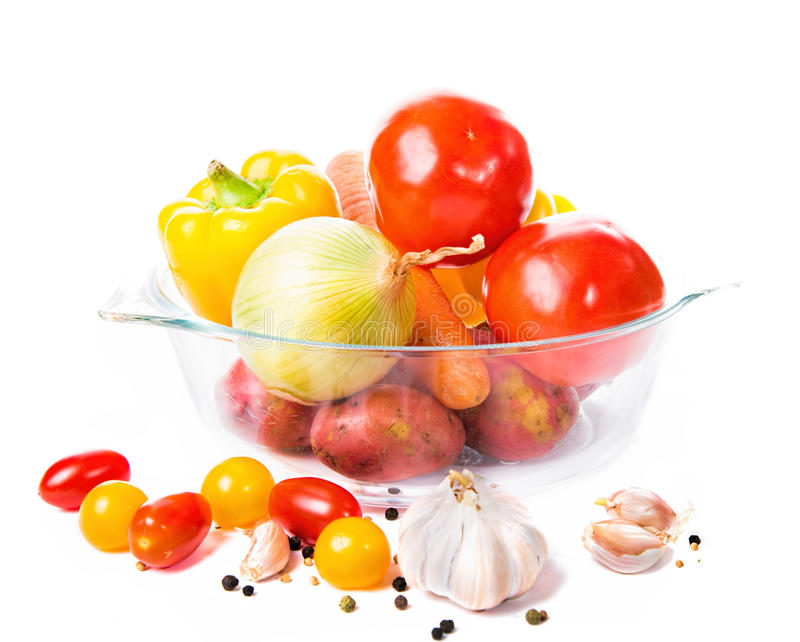 Vegetables in a glass pot isolated on white background. Fresh vegetables in a glass pot isolated on white background. Ready set for vegeterian dinner like stock photo