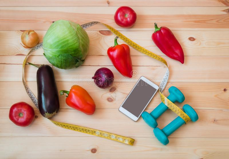 Vegetables, green dumbbells, smartphone and measuring tape. stock photos