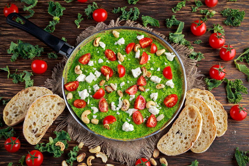 Vegetables Green Omelette with tomatoes, kale, greek cheese, olives, nuts, toast on wooden background. concept healthy stock photos