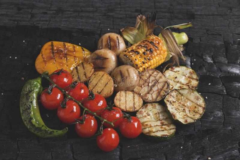 Vegetables grilled tomatoes pepper paprika corn potatoes mushrooms on charcoal. A royalty free stock images
