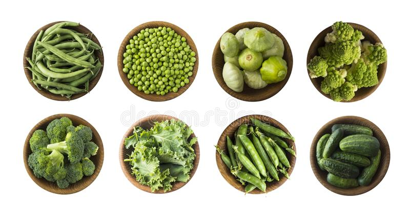 Vegetables isolated on a white. Squash, green peas, broccoli, kale leaves and green bean in wooden bowl. Vegetables with copy spac. E for text. Top view. Studio stock photo