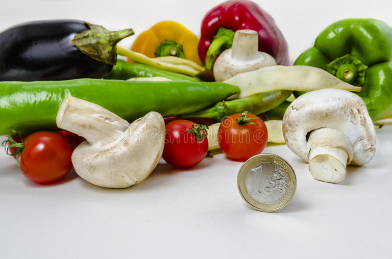 Vegetables and money. Vegetables low price concept-one euro coin next to vegetables shows how inexpensive healthy food is on white background royalty free stock photos