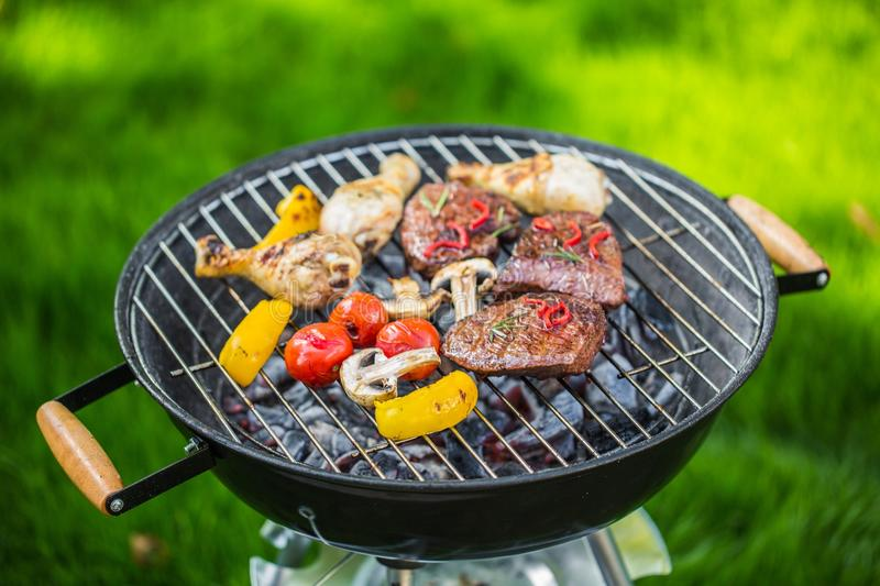 Vegetables and meat grilling outdoors in summer stock photography