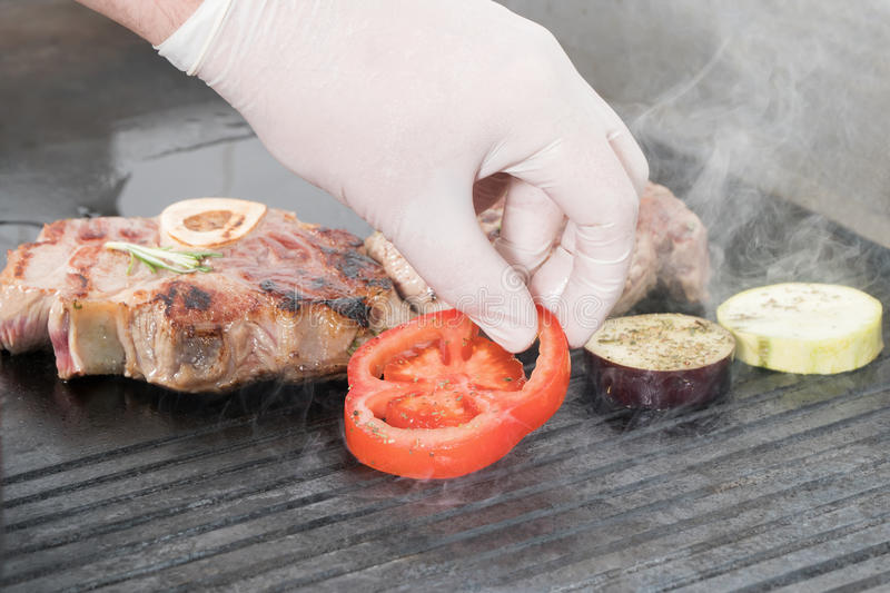 Vegetables and meat roasted on the barbecue. Male hand lays down tomato on smoking electric grill next to the meat steaks stock photos