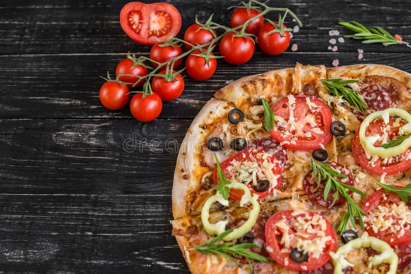 Vegetables, mushrooms and tomatoes pizza on a black wooden background. It can be used as a background royalty free stock photography