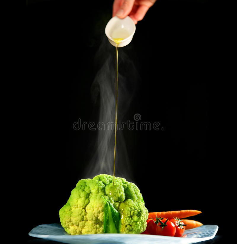Vegetables with olive oil dressing. This is a photo of steamed vegetables with a hand poring olive oil stock image