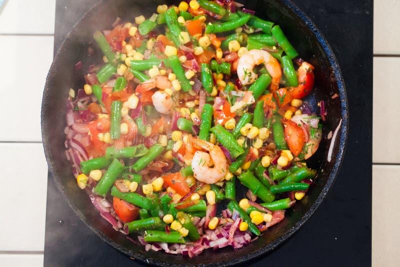 Vegetables in a pan, steam, top, green beans, onions, tomatoes, shrimp. Vegetables in a pan, steam, top, green beans onions tomatoes shrimp fried prawns stock photos