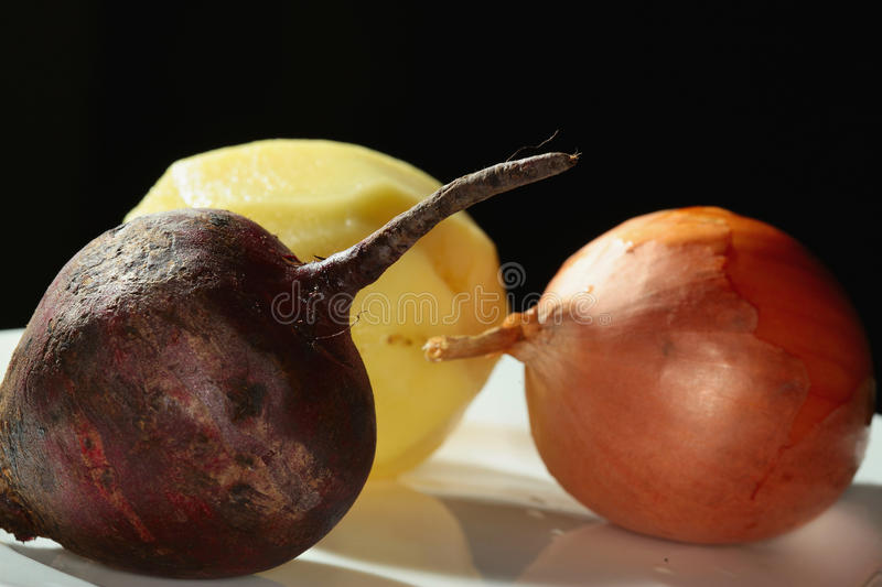 Vegetables on the plate. Macro onion, beet and potato on a white plate on a black background studio royalty free stock image