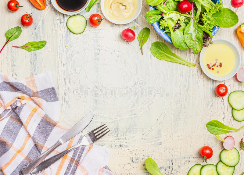 Vegetables salad preparation with dressings ,ingredients cutlery and kitchen checked napkin on light rustic background, top view stock photos