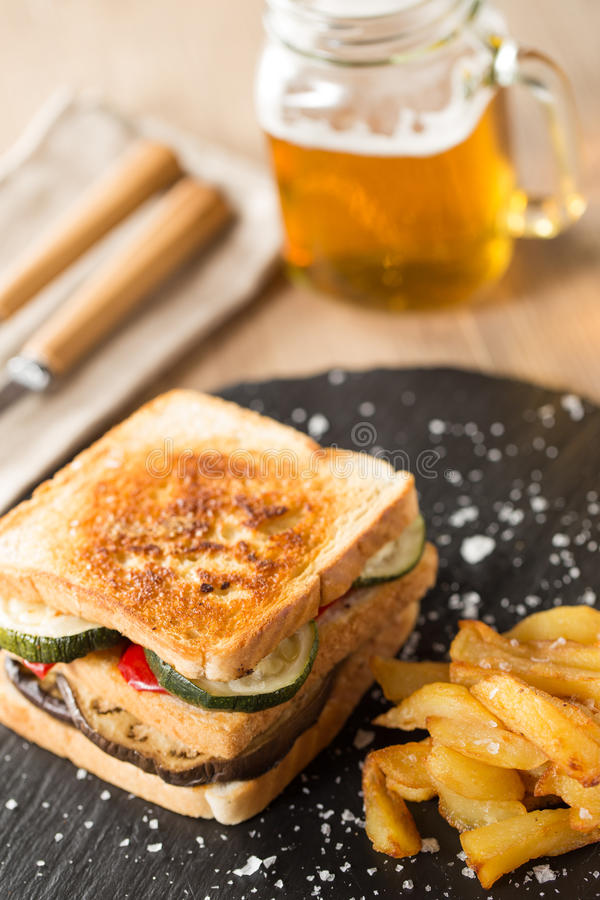 Vegetables sandwich. With glass of beer on a wood table stock photo