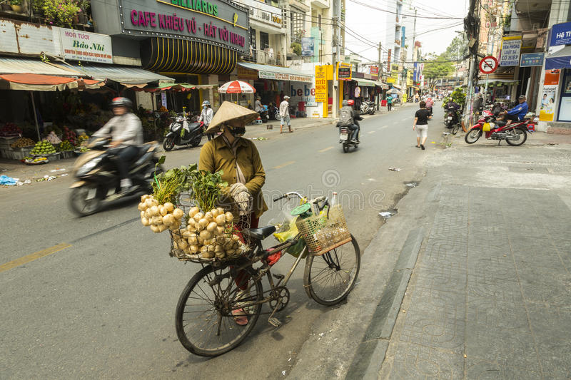 Vegetables seller in Vietnam. Woman selling wegetables from her bike on the street in District 3 in Ho Chi Minh city in Vietnam royalty free stock photography