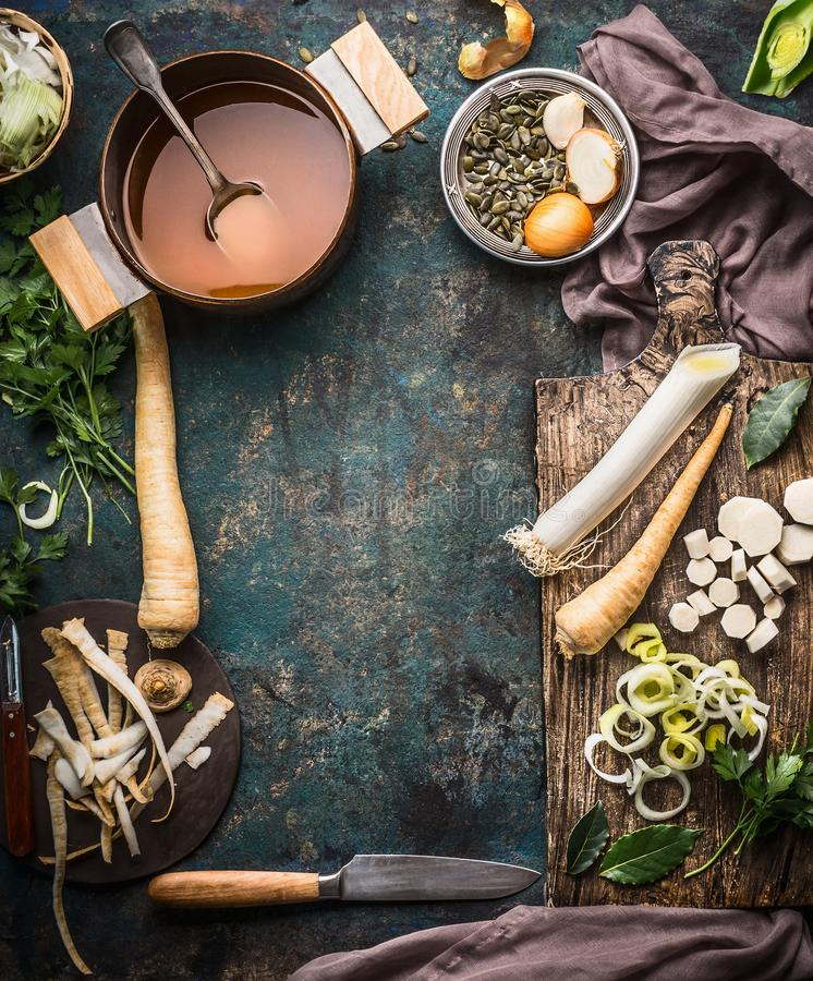 Vegetables soup cooking preparation with parsnip and leek on rustic kitchen table background with ingredients, pot , vegetable bro. Th, knife and cutting board royalty free stock photos