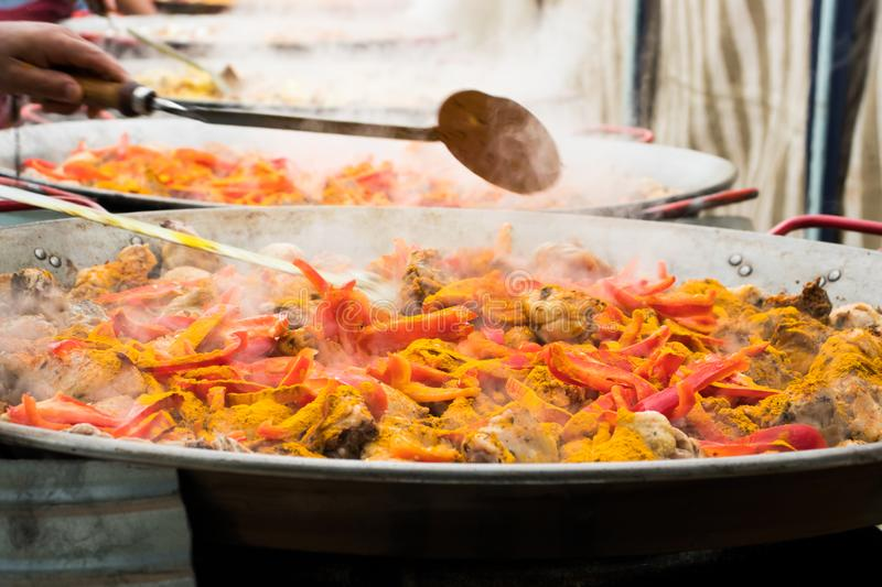 Vegetables, spices and chicken meat are steamed in giant pans to prepare a collective paella.. royalty free stock image