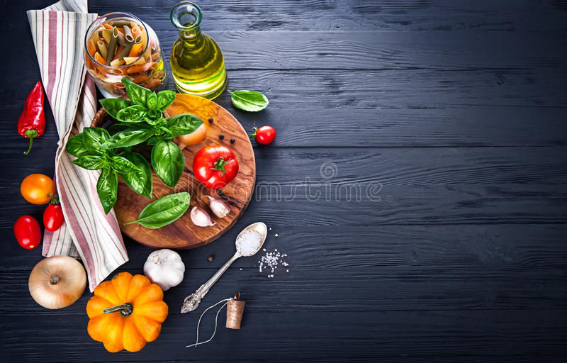 Vegetables and spices ingredient for cooking italian food. On black wooden old board in rustic style royalty free stock photo