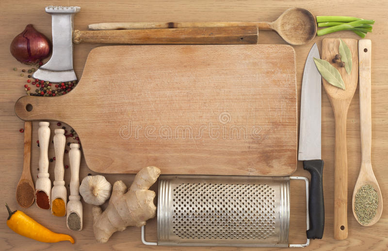 Vegetables and spices in kitchen. Vegetables and spices border and empty cutting board stock photography