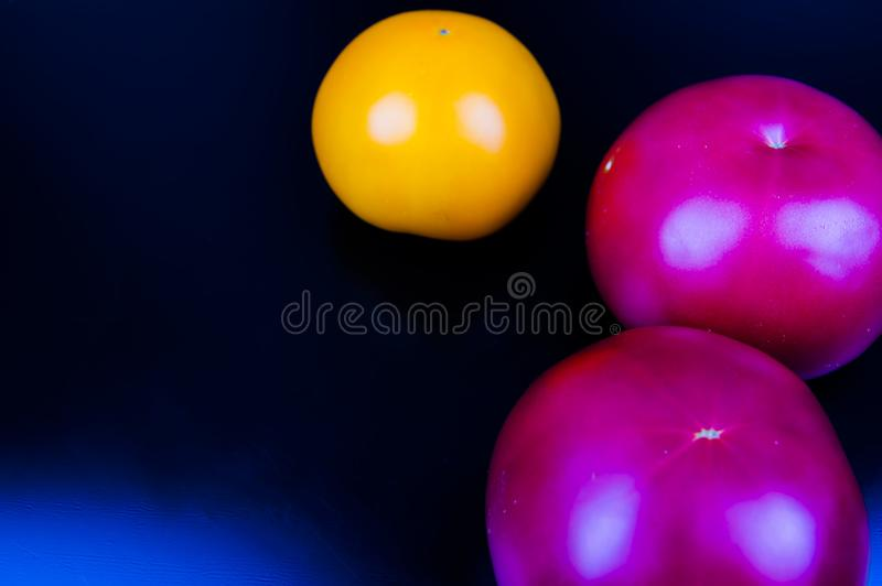 Vegetables tomatoes on a black background. Food royalty free stock photo