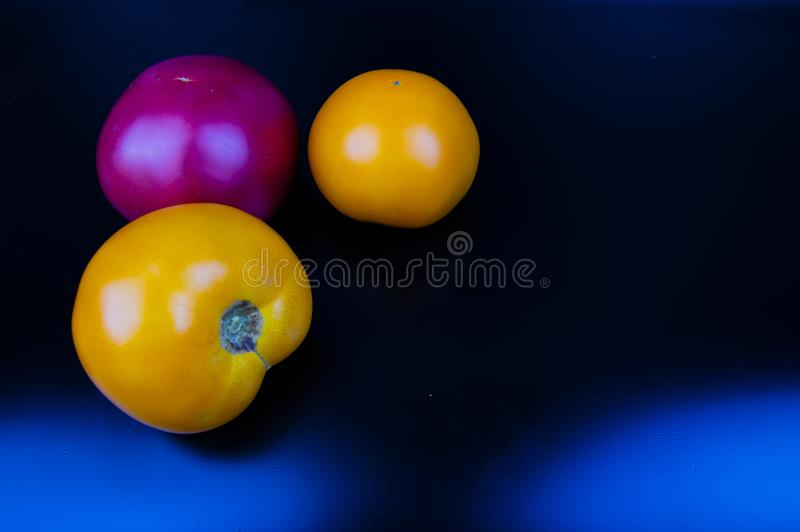 Vegetables tomatoes on a black background. Food stock photo