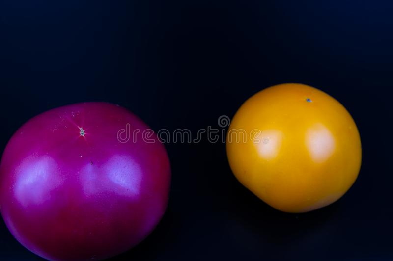 Vegetables tomatoes on a black background. Food stock images