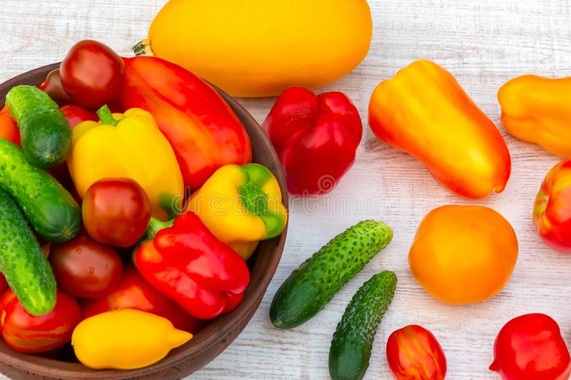 Vegetables: tomatoes, cucumbers, paprika, pepper, zucchini in a clay bowl and on a white wooden table. Ingredients for stock photos