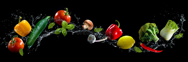 Vegetables water splash. Vegetables on black background with water splash stock photography