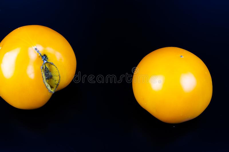 Vegetables yellow tomatoes on a black background stock photo
