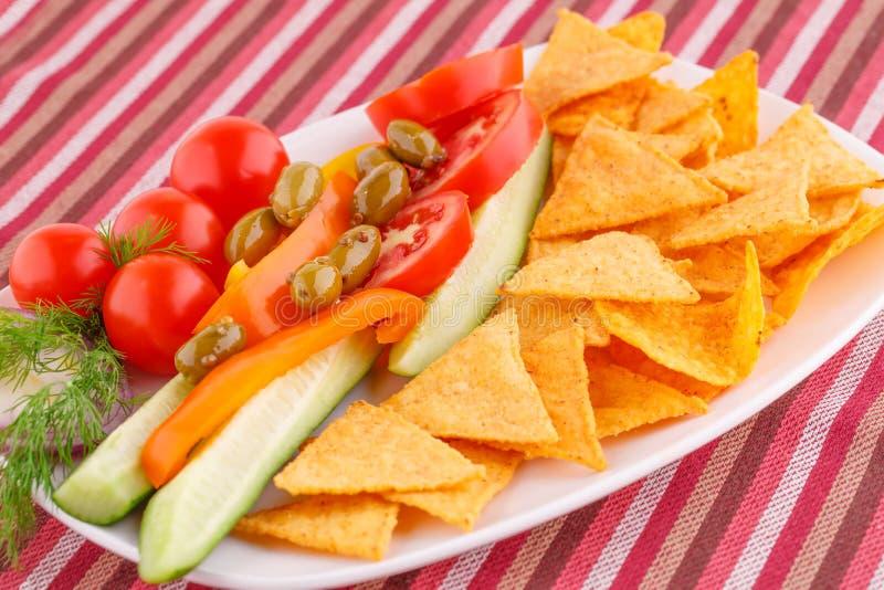 Vegetais, azeitonas, nachos na placa imagem de stock royalty free