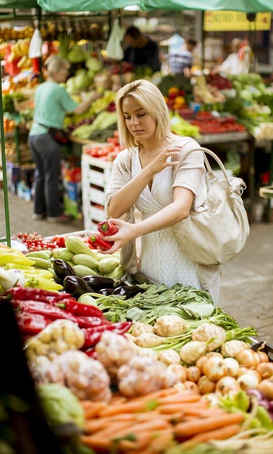 Vegetais bonitos da compra da jovem mulher no mercado fotografia de stock royalty free
