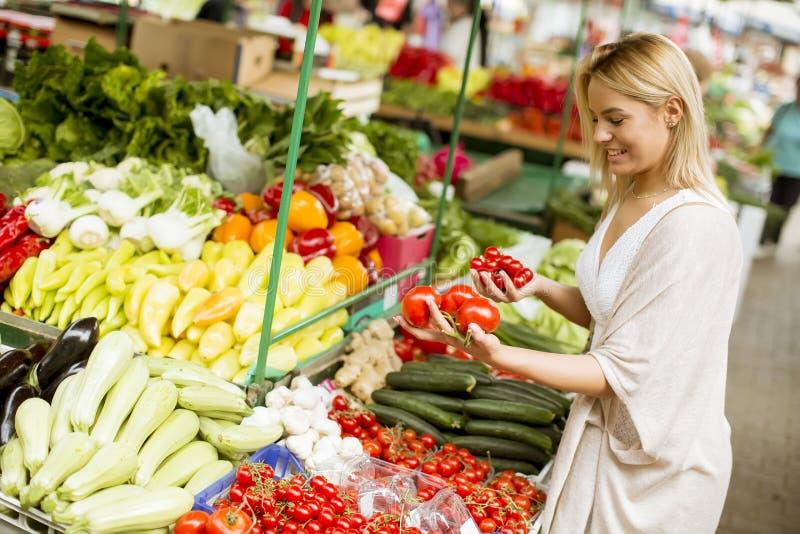 Vegetais bonitos da compra da jovem mulher no mercado imagem de stock royalty free