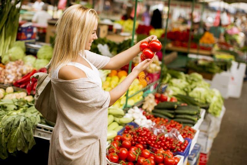Vegetais bonitos da compra da jovem mulher no mercado foto de stock royalty free