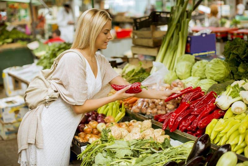 Vegetais bonitos da compra da jovem mulher no mercado fotos de stock royalty free