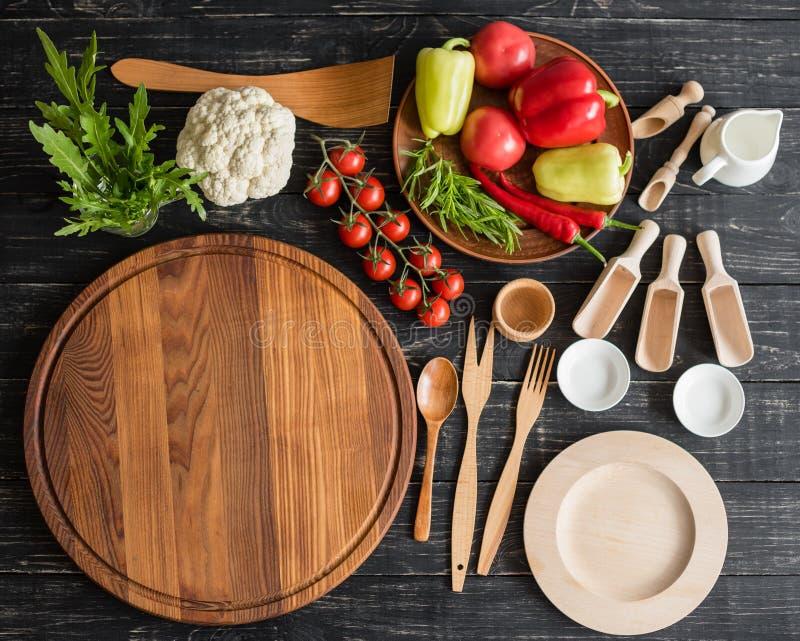 Vegetais, cogumelos e pizza dos tomates em um fundo de madeira preto imagem de stock